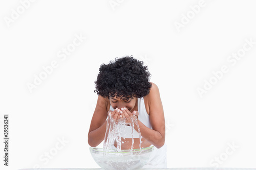 Young woman rinsing her face with water