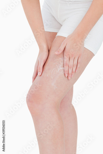 Woman applying cream on her thigh