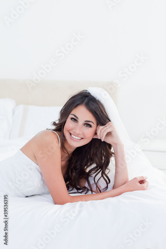 Young smiling bribe lying on her bed with her hand on her temple