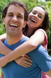 Young smiling woman standing in a park with her arms wrapped around her boyfriend