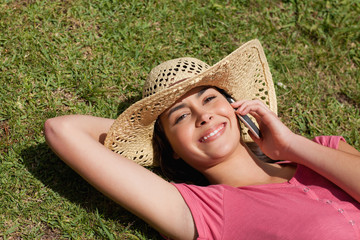 Young attractive woman lying on the grass while talking on the phone