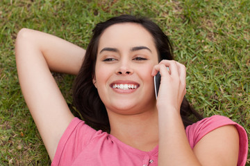 Overhead view of a young smiling woman talking on the phone
