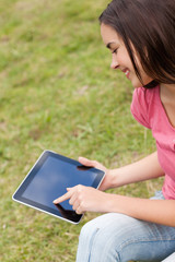 Smiling attractive young girl using her tablet computer in a park