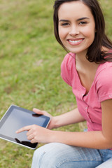 Young smiling woman looking at the camera while using her tablet pc