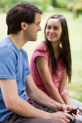 Young couple sitting in a park while talking together