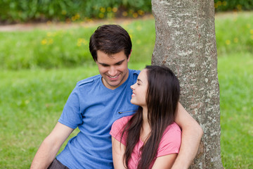 Young smiling couple sitting together against a tree