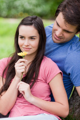 Young woman smelling a flower while being accompanied by her boyfriend