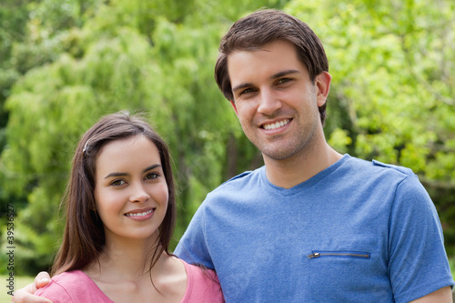 Young smiling couple standing side by side in a park