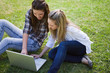 Young girls sitting on the grass while looking at a laptop