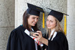 Young smiling graduating student photographing herself and a friend