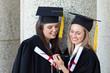Young smiling graduating girls looking at a digital camera