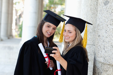 Young smiling girls photographing themselves with caps and gowns