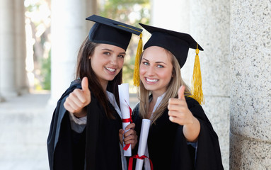 Smiling graduating students putting their thumbs up