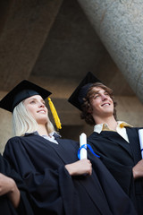 Low-angle view of happy graduating students