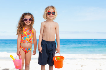 Children with sunglasses standing on the beach