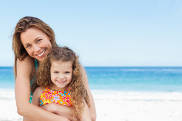 Smiling mother hugging her daughter on the beach