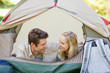 A smiling couple lying in their tent