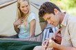A man playing a guitar for his girlfriend who is inside the tent