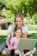 Smiling mother and daughter with a laptop while looking ahead