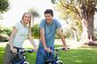 A smiling couple sitting on their bikes