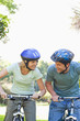 Smiling couple looking at each other with helmets on