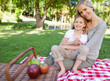 A mother and daughter sitting on a blanket with a picnic and some apples