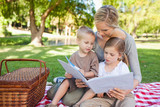 A mother and her kids read a book together in the park
