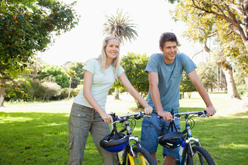 Couple standing with their bikes in the park