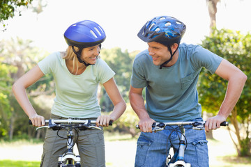 Smiling couple on their bikes while wearing helmets