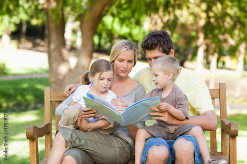 A family sitting on the park bench while reading a book