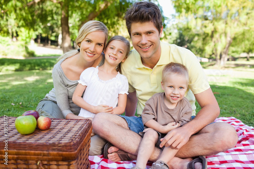 Happy family looking at the camera while having a picnic