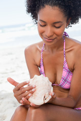 Young woman looking at a shell while sitting on the beach