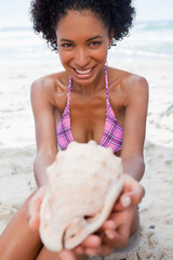 Young woman holding a shell while sitting on the beach