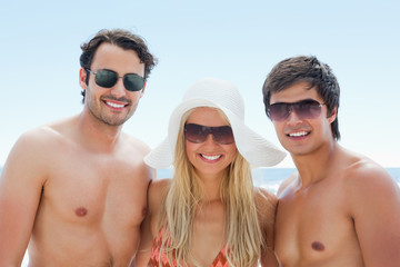 Three freinds smiling as they wear sunglasses
