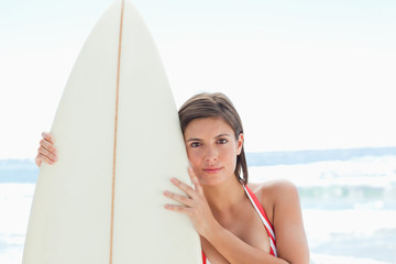 Woman with a serious expression holding a surfboard