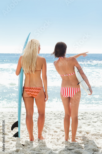Woman with surfboard beside a woman pointing out to the ocean