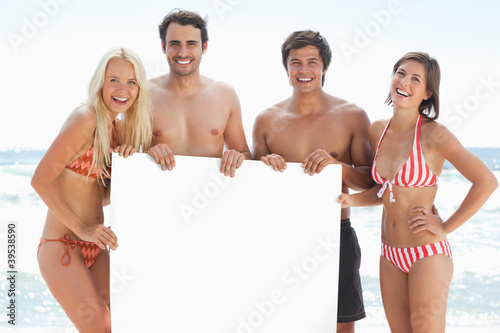 Four friends in swimsuits smiling as they hold a blank poster