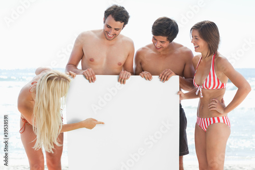 Woman pointing at a blank poster while holding it with her three friends
