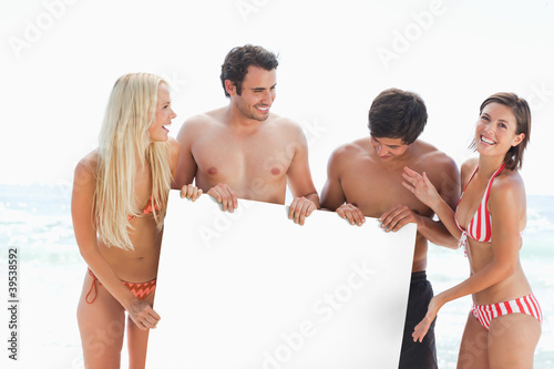 Four friends laughing as they stand while holding a large blank poster