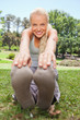 Smiling sportswoman stretching on the lawn