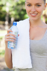 Smiling athletic woman with a bottle of water in the park