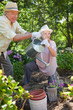 Man and a woman smiling while watering flowers