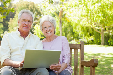 Two friends looking ahead as they hold a laptop while sitting on a bench