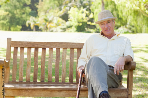 Man looking ahead while sitting down on a bench as he holds a cane