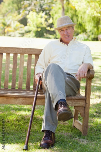 Man smiling while siting on a bench as he hold a cane