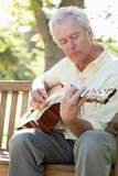 Man with his eyes closed while playing the guitar as he sits on a bench