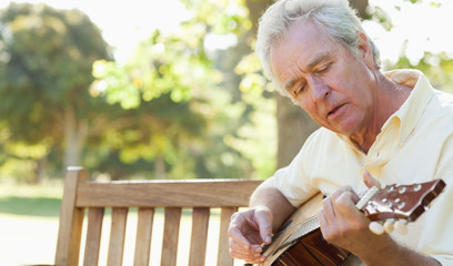 Man singing a song while playing a guitar as he sits on a bench