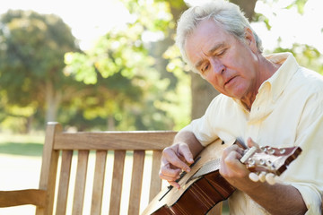 Man looking at a guitar as he is playing it while he sits on a bench