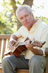 Man looking towards the side while playing the guitar on a bench