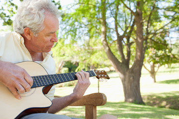 Man plays a guitar while sittng on a bench with a tree in the background